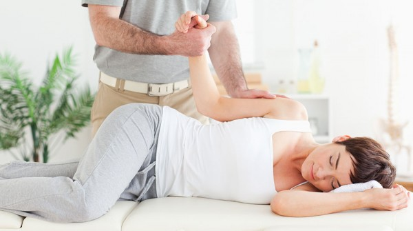 Chiropractor stretches female customer's arm
