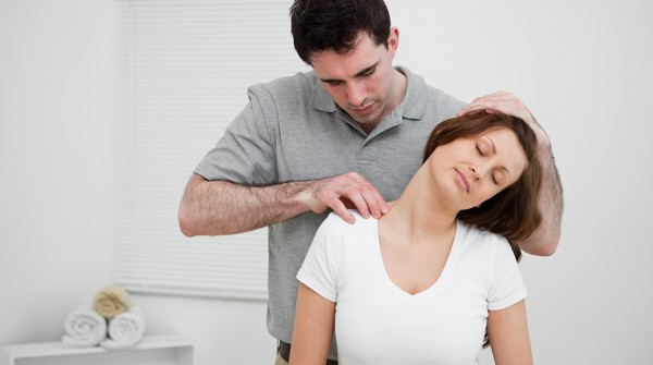 Serious osteopath palpating the trapezius of a woman