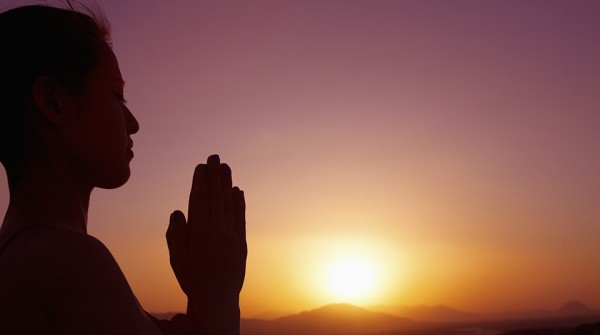 Serene young woman doing prayer pose in the desert